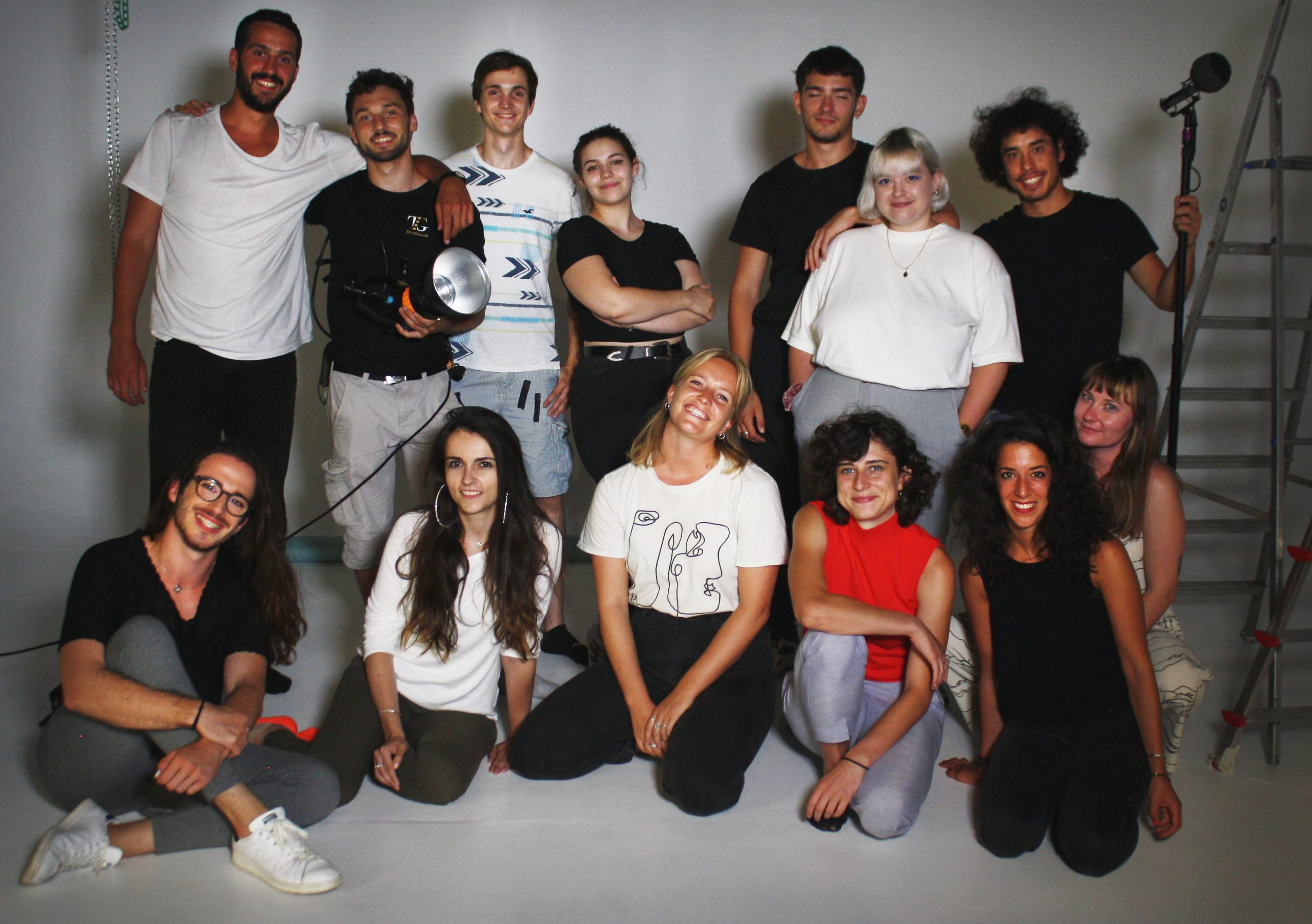 The young people who worked on the new video are posing for a group photo, smiling at the camera. Seven young people stand at the back of the shot with six in a second row in front of them, kneeling.